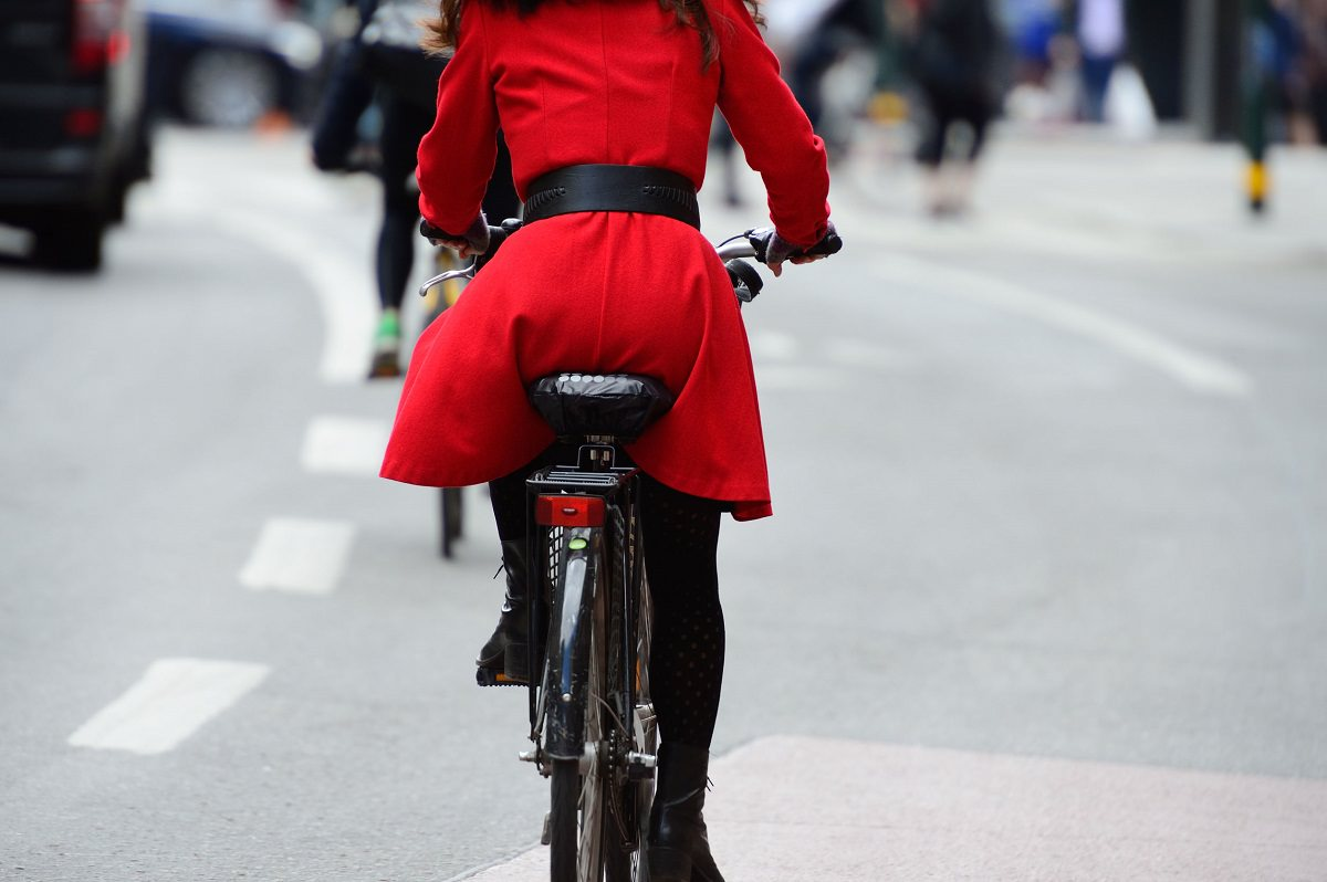 Woman with red jacket cycling