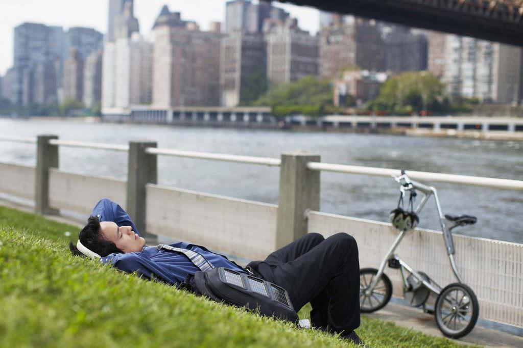 Man relaxing next to folding bike