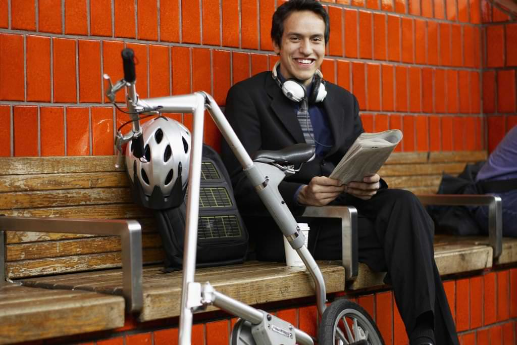 Smiling man with a folding bike