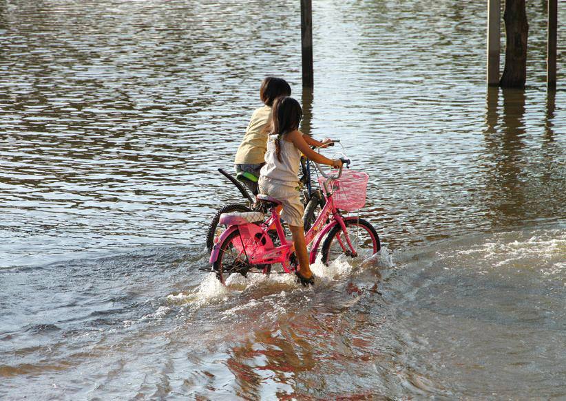Children riding bikes in rain
