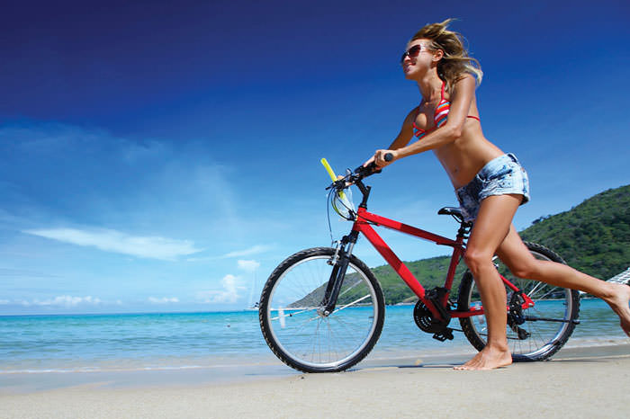 Lady with bicycle in beach