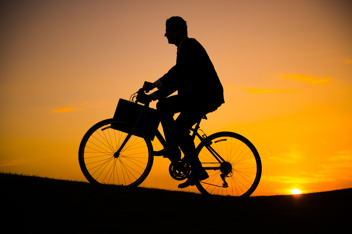 Business man riding bike on the hill