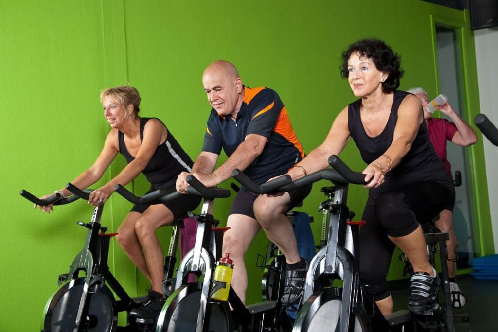 Three people on indoor cycles