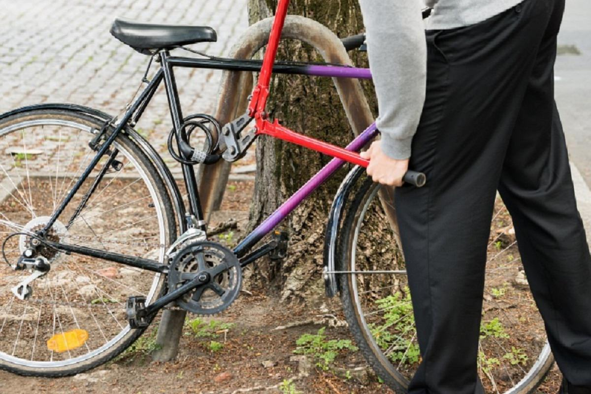 Thief trying to break bike lock with pliers