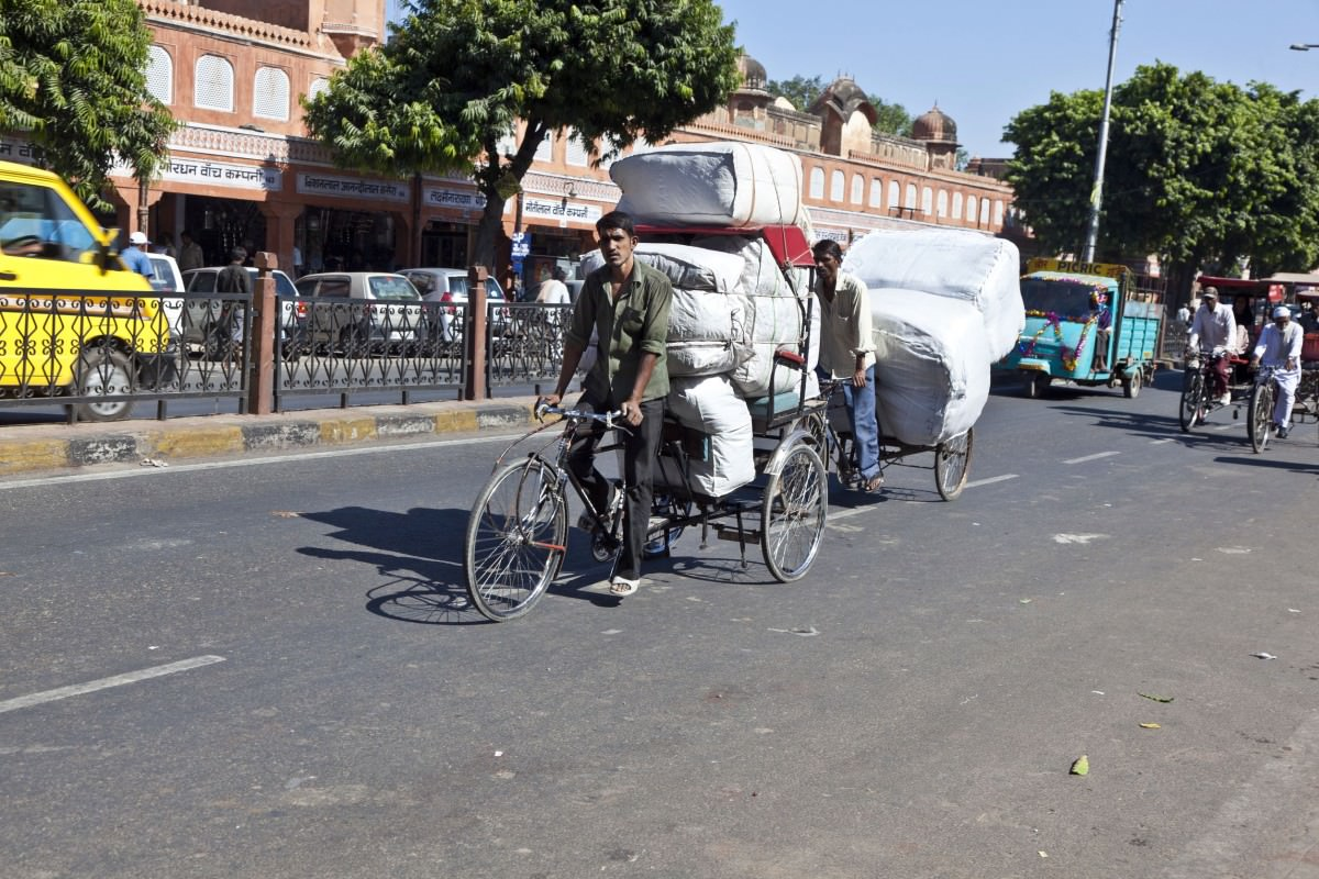 Man cycling a rickshaw with loaded cargo