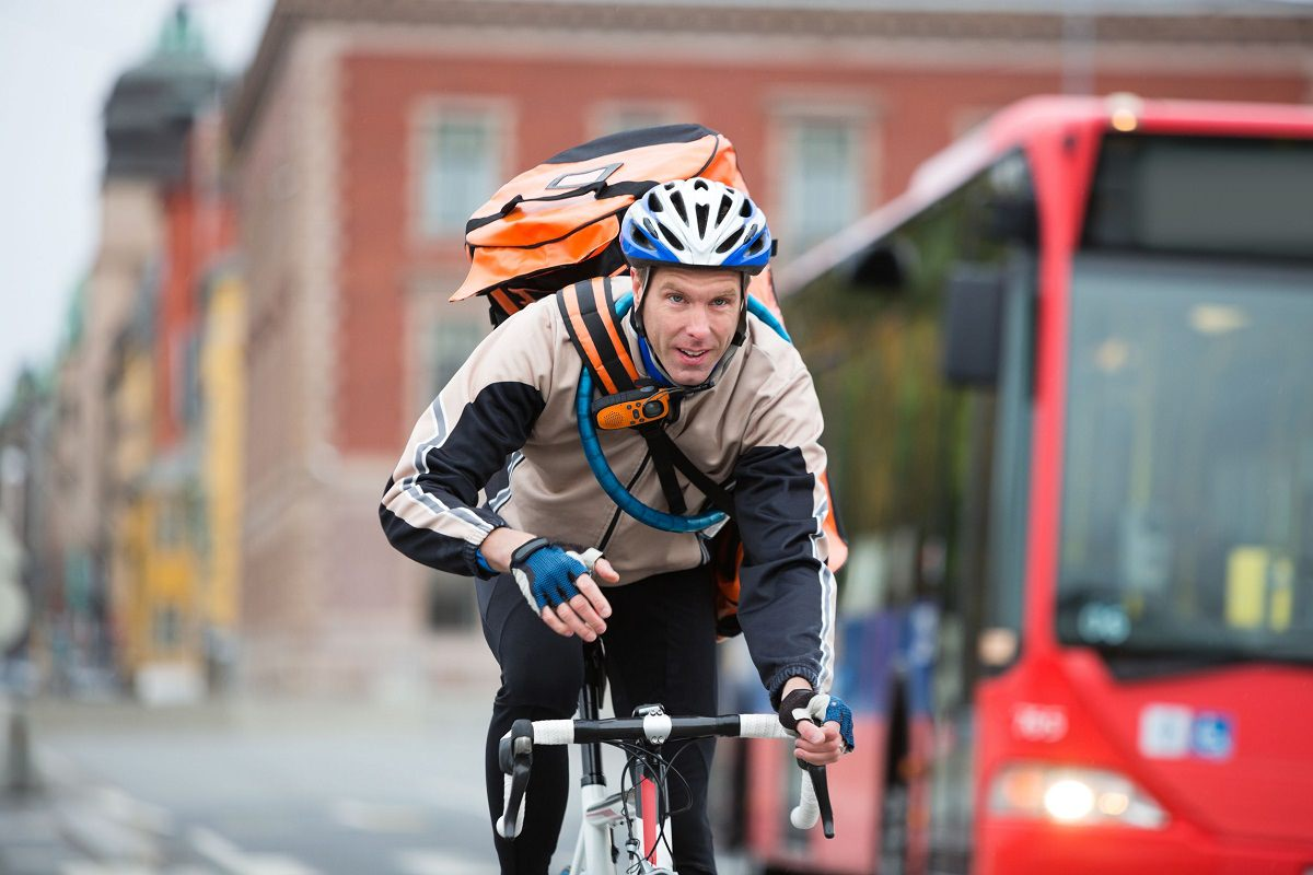 Man cycling with courier delivery bag