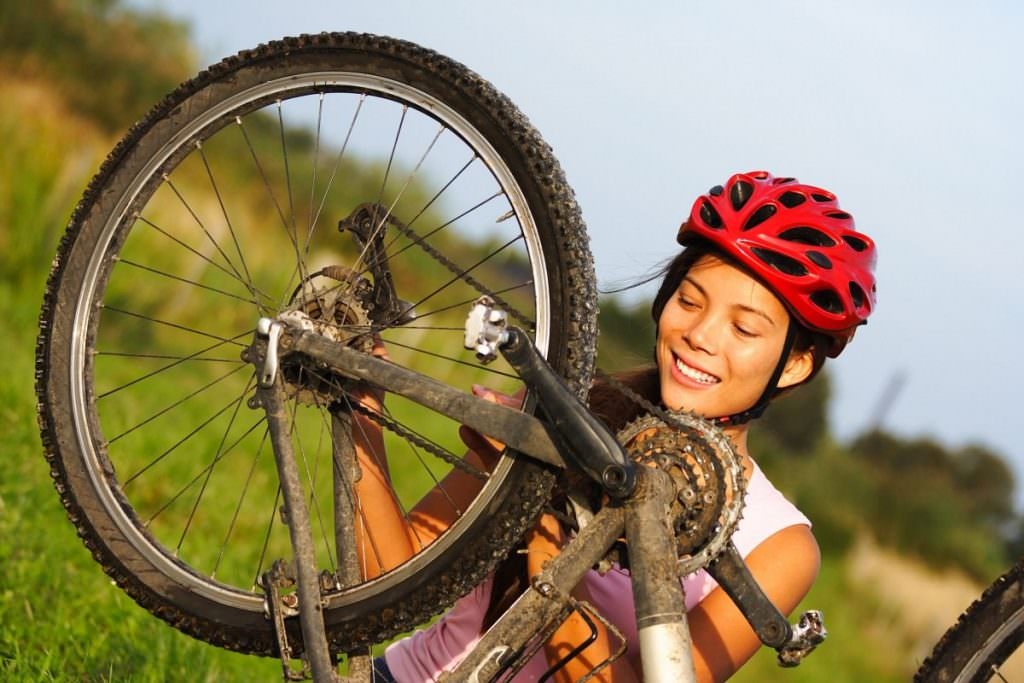 Woman fixing mountain bike wheel
