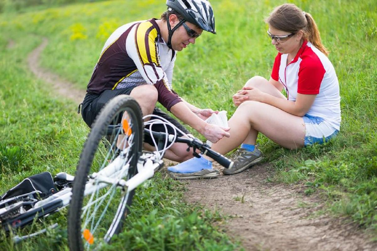 Woman being applied first aid due to bike accident