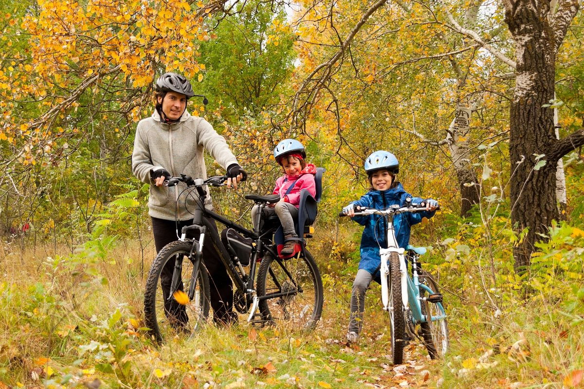 Father and children cycling together