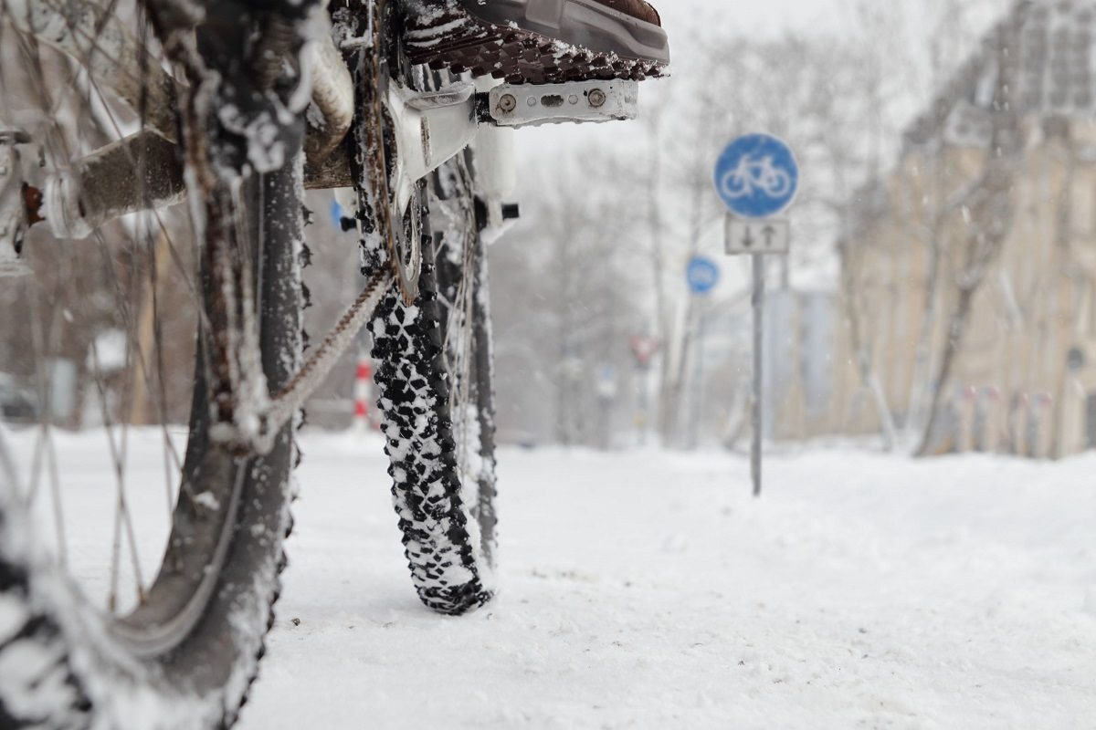 Rider rides bicycle in snow