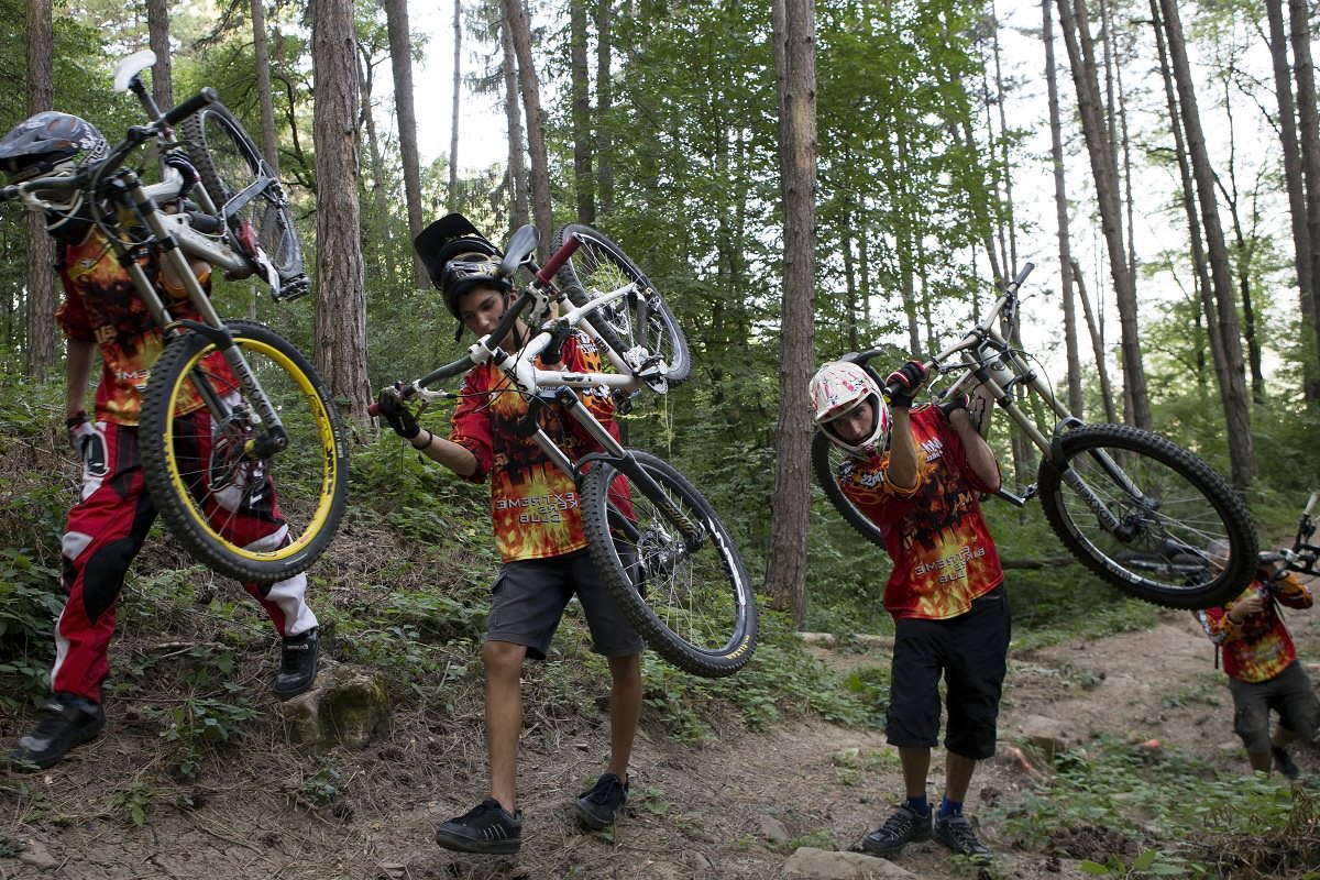 Mountain bikers carrying their bikes