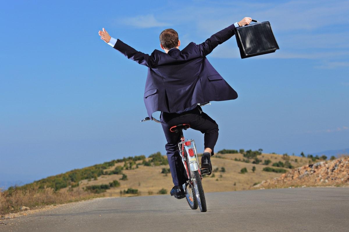 Carefree businessman on a bike