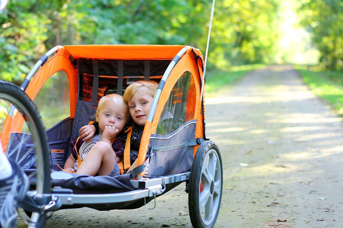 Two children in a bike trailer